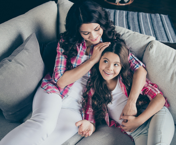 Close up top above high angle view photo calm two people mum proud little daughter tell speak school things good marks wear pink plaid shirts flat apartment room sit lying cozy couch sofa divan