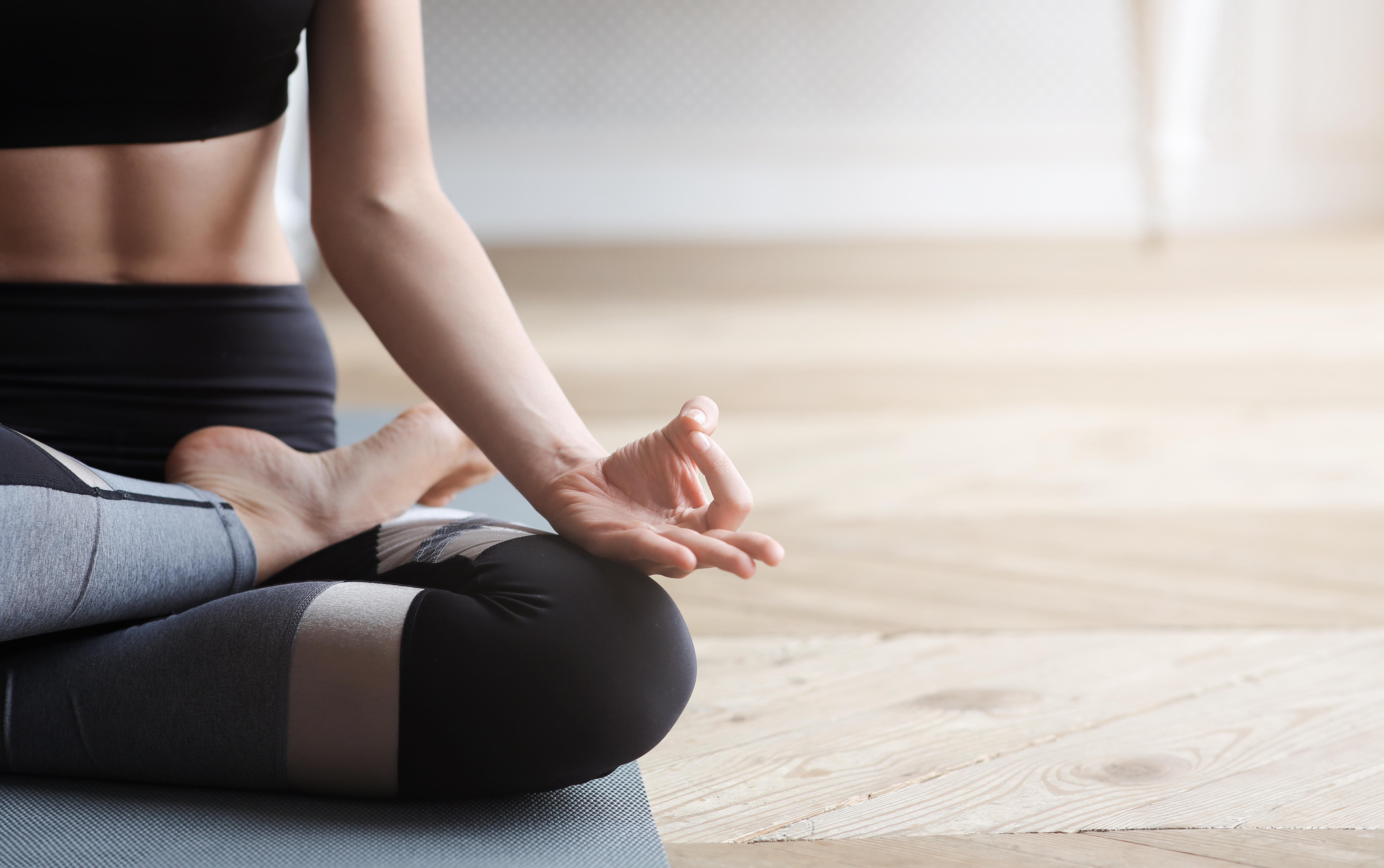 Yoga, meditation, pilates concept. Close up of yoga woman sitting in lotus pose on wooden floor, copy space